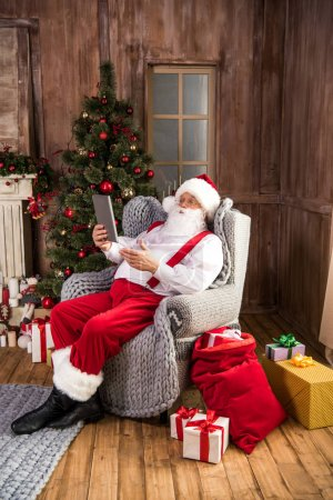 Photo for Santa Claus sitting in armchair using digital tablet an pointing - Royalty Free Image