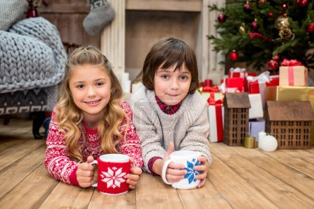 Photo for Happy kids lying on floor with mugs and looking at camera - Royalty Free Image