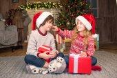 Děti v Santa klobouky s vánoční dárky
