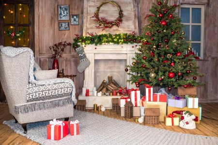 Photo for Empty grey armchair with pile of gift boxes under Christmas tree - Royalty Free Image