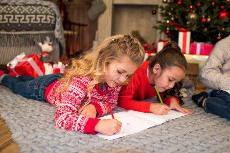 Photo pour Enfants se trouvant sur la moquette grise et dessin - image libre de droit