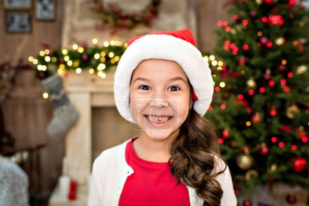 Photo for Kid in Santa hat with happy expression looking at camera - Royalty Free Image