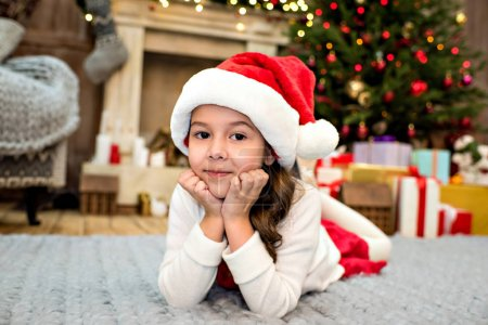 Photo for Kid in Santa hat lying on carpet with happy expression - Royalty Free Image