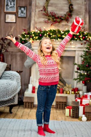 kid rising arms up with gift box