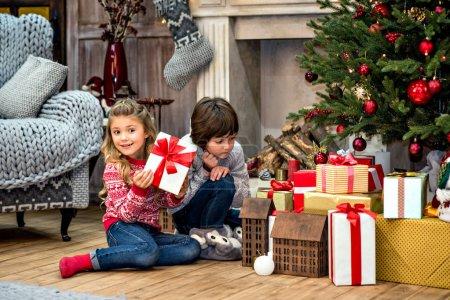 Foto de Niños felices sentados junto a la chimenea con la pila de cajas de regalo bajo el árbol de Navidad - Imagen libre de derechos