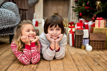 Photo for Happy kids lying on floor near a pile of gifts and looking at camera - Royalty Free Image