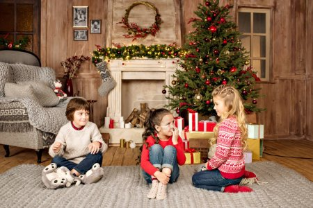 kids sitting on carpet with Christmas gifts