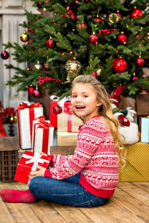 Photo for Happy kid sitting on floor with Christmas gift box in hands - Royalty Free Image