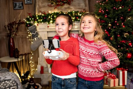 Photo for Happy children standing near fireplace and using hexacopter drone - Royalty Free Image