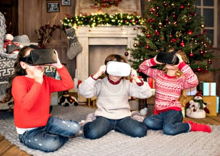 Photo for Children sitting on carpet and using virtual reality headsets - Royalty Free Image