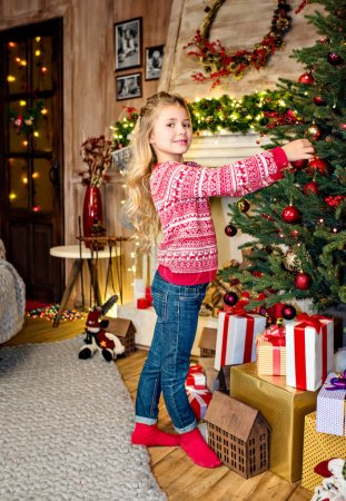 Photo for Happy kid decorating fir tree and looking at camera - Royalty Free Image