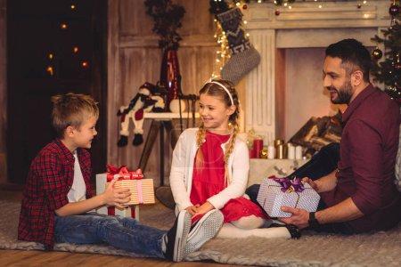 Photo pour Joyeux famille assis sur le sol avec des cadeaux de Noël - image libre de droit