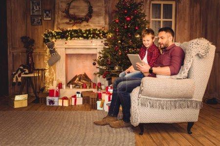 Photo pour Père et fils souriants utilisant une tablette numérique au moment de Noël - image libre de droit
