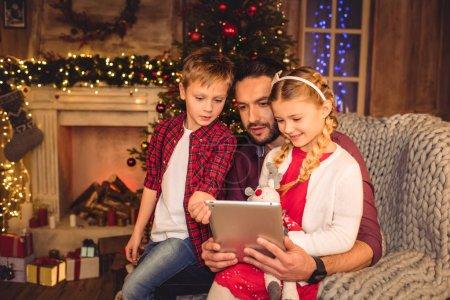 Photo pour Père avec enfants assis dans un fauteuil gris et utilisant une tablette numérique - image libre de droit