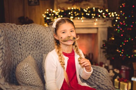 Girl holding moustache on stick