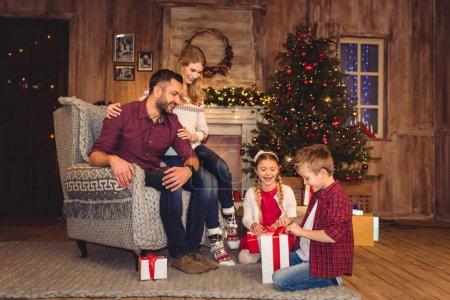 Photo pour Cadeaux d'ouverture de famille heureux dans une chambre confortable décorée pour Noël - image libre de droit