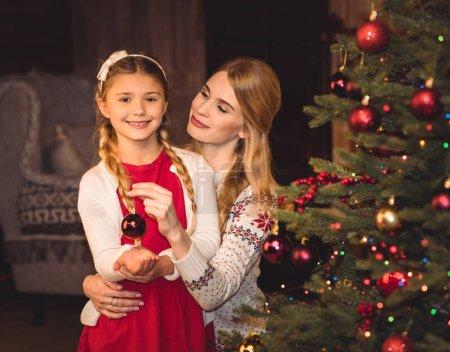 Photo pour Sourire, mère et fille, décorer le sapin de Noël - image libre de droit