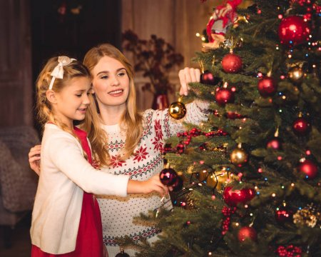 Photo for Smiling mother and daughter decorating christmas tree - Royalty Free Image