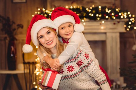 Photo for Happy mother and daughter in santa hats hugging and smiling at camera - Royalty Free Image