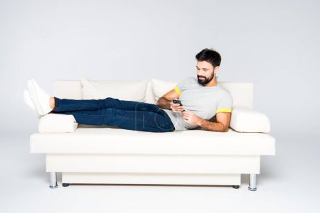 Photo for Bearded man lying on white couch and using smartphone - Royalty Free Image