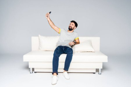 Photo for Bearded man sitting on white couch and taking selfie - Royalty Free Image