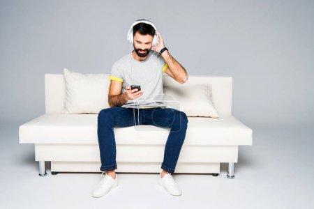 Photo pour Homme barbu dans les écouteurs blancs assis sur le canapé et écoute la musique avec smartphone - image libre de droit