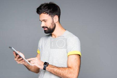 Photo pour Homme barbu souriant utilisant une tablette numérique isolée sur gris - image libre de droit