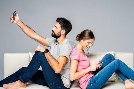 Photo pour Jeune couple assis dos à dos sur un canapé blanc et utilisant des smartphones isolés sur gris - image libre de droit