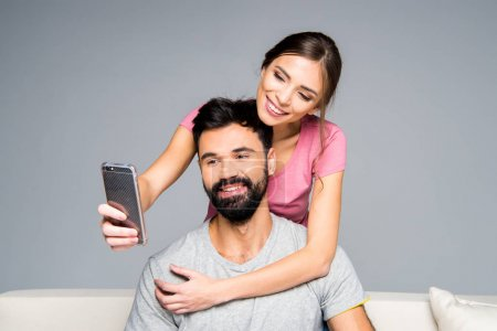 Photo for Happy couple taking selfie while hugging on white couch isolated on grey - Royalty Free Image
