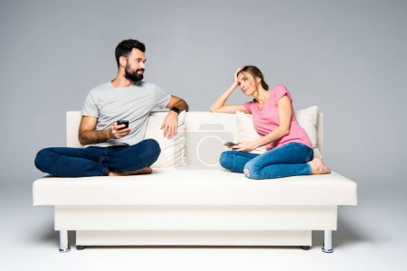 Photo pour Young couple sitting on white couch and using smartphones isolated on grey - image libre de droit