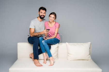 Photo for Young couple sitting on white couch and using smartphones isolated on grey - Royalty Free Image