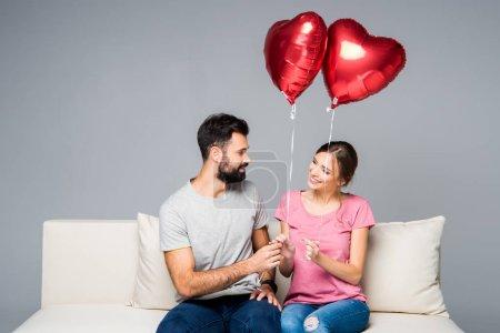 Photo pour Couple souriant assis sur un canapé blanc avec des ballons rouges en forme de coeur isolés sur gris - image libre de droit