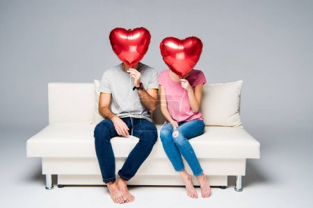 Photo for Couple sitting on white couch with red heart-shaped balloons isolated on grey - Royalty Free Image