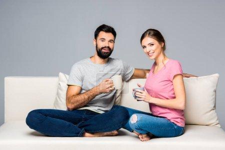 Photo pour Couple souriant assis sur le canapé et tenant des tasses isolées sur gris - image libre de droit