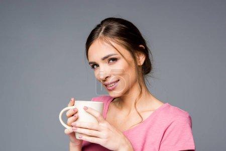 Photo pour Femme tenant une tasse blanche et regardant la caméra isolée sur gris - image libre de droit