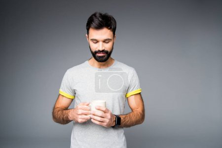 Man holding white cup