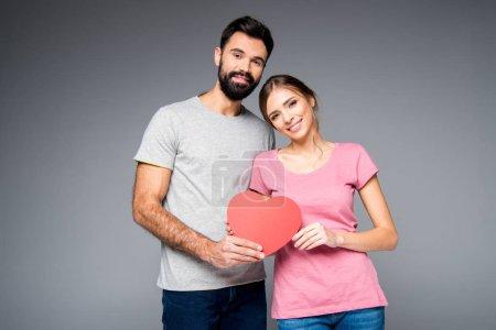 Photo pour Jeune couple posant avec du papier rouge coeur isolé sur gris - image libre de droit