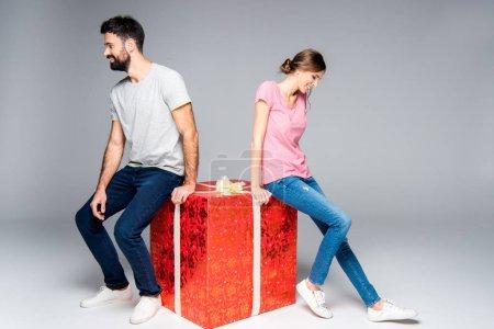 Photo pour Jeune couple souriant assis sur une grande boîte cadeau rouge isolé sur gris - image libre de droit