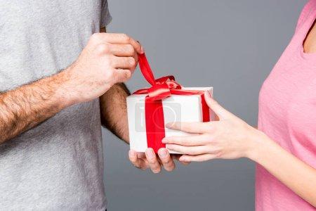 Photo pour Vue partielle du couple heureux debout avec boîte cadeau isolé sur gris - image libre de droit