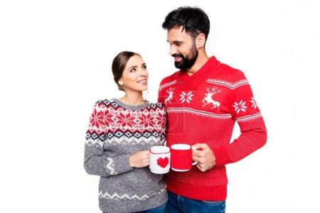 Photo pour Couple de chandails tricotés tenant des tasses avec des boissons chaudes, isolés sur blanc - image libre de droit