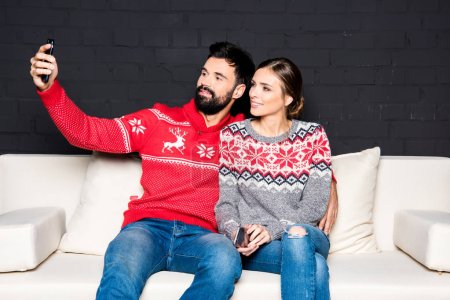 Photo for Couple in colorful sweaters taking selfie while sitting on white couch - Royalty Free Image