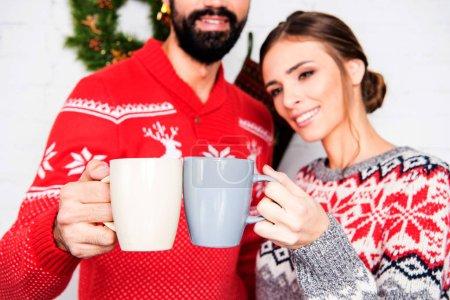 Photo pour Heureux couple portant des chandails de Noël, grillage avec tasses - image libre de droit