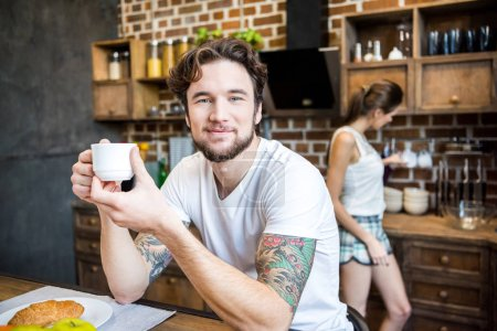 Photo for Smiling man in white t-shirt drinking coffee in kitchen and looking at camera - Royalty Free Image