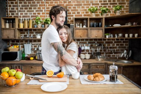 Photo for Happy young couple hugging in kitchen at morning - Royalty Free Image