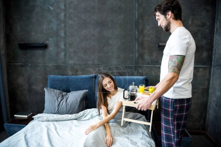 Photo for Young man brings breakfast in bed for his pretty girlfriend - Royalty Free Image