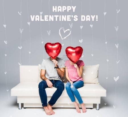 Photo pour Couple assis sur un canapé blanc avec des ballons rouges en forme de coeur isolés sur gris - image libre de droit