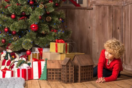 Photo for Little kid sitting near pile of gift boxes under Christmas tree - Royalty Free Image