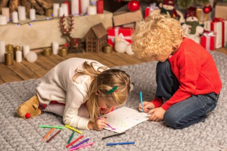 Photo pour Enfants assis sur la moquette grise et dessin - image libre de droit