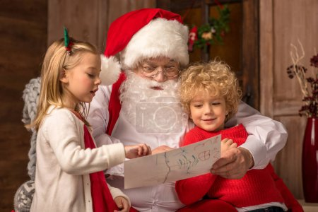 Children showing picture to Santa Claus