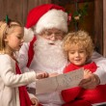 Portrait of happy children showing picture to Santa Claus